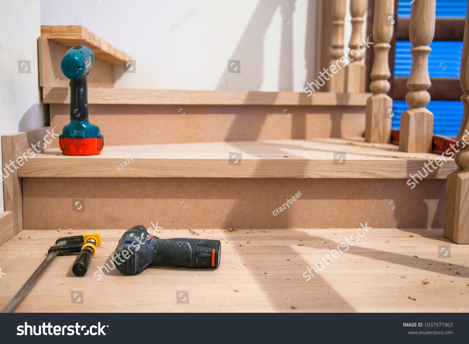 stock-photo-manufacturing-repair-of-wooden-stairs-in-a-residential-building-1037971963