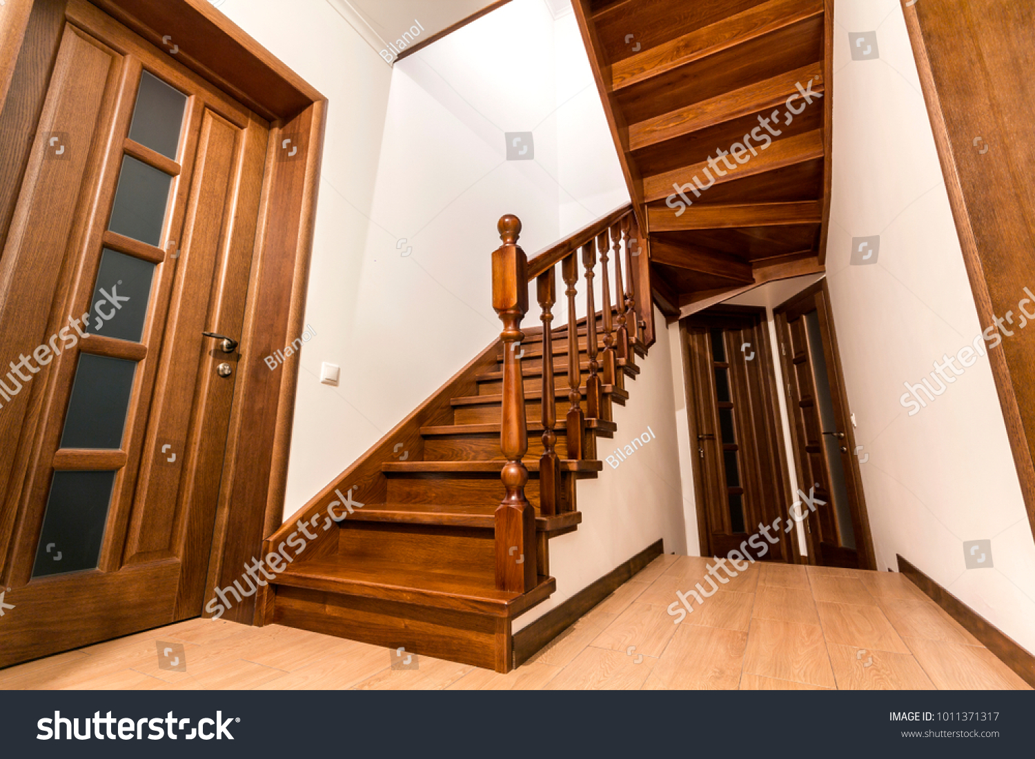 stock-photo-modern-brown-oak-wooden-stairs-and-doors-in-new-renovated-house-interior-1011371317